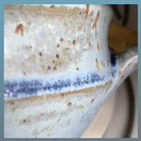 Der Ausschnitt einer Tasse zeigt grau bläuiche bis hellgau bläuliche Bereiche. Über dem Knickrand der Tasse ist die Glasur mittelblau glänzend, genau auf der Kante bräunlich grau und dazwischen und auf den Flächen hellblau, auch lila grau . Alles ist durchsetzt mit den kleinen brauen Spots, die das Oberflchenbild zudem auflockern.