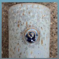 Die obere Hälfte eines Bechers mit Siegelstempel. der STempel hat das Motiv einer Spirale und ist deutlich dunkelblau glänzend. die Gfäßoberfläche ist hellblau blaulila lilagrau melliert. die markanten brauen Spots lockern die oberfläche auf.