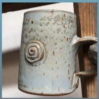 Diese Espressotasse ist eher dünn glasiert und somit verweilen die Farben zwischen hellblau und zartgrau sowie lilabraun. Der markante Siegelstempel hat ebenfalls diese Farbschattierungen. Kleine braune Punkte sind unregelmäßig verteilt wie bei einem Vogelei. Der Gesammteindruck der Farbwiedergabe ist: kühl blaß hellblau