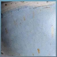 Die Detailansicht einer Tasse zeigt eine ebenmäßige matte Oberfläche in hellblau. Sie ist übersäht mir braunen Punkten, von denen manche zu feinen kurzen Strichen zerlaufen sind.
