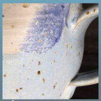 Gezeigt wird der Ausschnitt einer Tasse. Es gibt einen hellblau und einen weiß glasierten Teil. Da wo sich die Glasuren überschneiden sieht die Glasur mittelblau glänzend aus. Braun orangene Spots übesäen die Oberfläche.