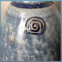 Die Detailansicht eines Flaschenhalses offenbart, daß die Glasur sowohl hellblau matte , als auch dunkelblau glänzende Oberflächen hervorbringen kann. An Kanten und Stempeldekor ergeben sich tiefere und glänzendere Farben. Die Spots zeigen sich in orangenen verwischten kurzen Strichen und brauen Punkten und Pünktchen.