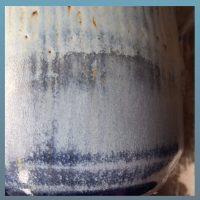 Die Detailansicht einer Vase zeigt unterschiedliche Bereiche in denen die Glasur hellblau matte, dunkelblau glänzende und weitere Farbabstufungen in blau angenommen hat. Zum Til sind braune Spots sichtbar.