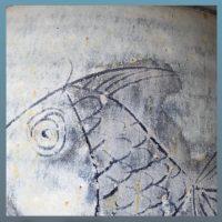 Die Ritzzeichnung eines Fisches ist mittelblau glänzend auf lebendig hellblauem Hintergrund zu sehen. längst nicht immer ist das Motiv so gut sichtbar wie hier.